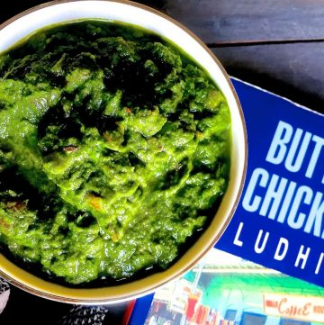 Sarson ka saag, the classic winter curry from the punjab. Shown in a white bowl with a book on Butter Chicken in Ludhiana, alongside