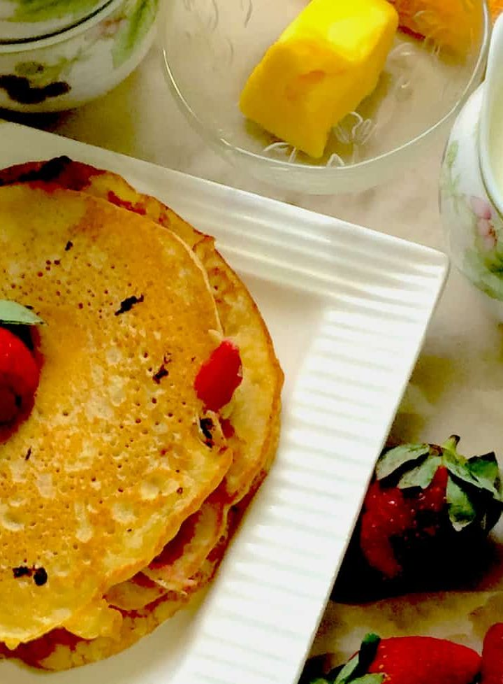 Really Easy Strawberry Buttermilk pancakes on a white square edged plate with a strawberry on top, syrup, milk and butter in little flowered cups alongside