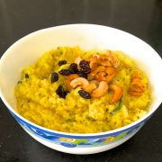 Ven Pongal the delicious tamil version of khichdi. Garnished with fried cashew nuts and raisins, rice and moong dal lentils cooked together with turmeric, served in a white bowl patterned with blue and yellow