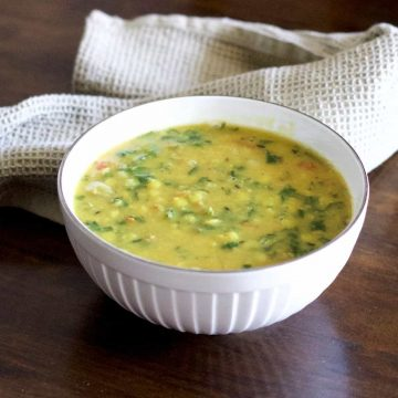 Yellow split Lentils and green spinach stew with red tomatoes, Arhar Dal Palak in a white bowl with a grey green napkin at the back, on a dark wooden surface