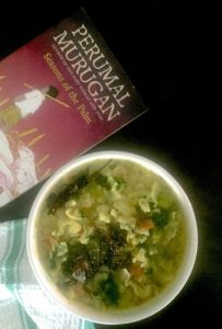 Easy green cabbage stew with vegetables, lentils and coconut, in a white bowl. Tempered with mustard, chili, cumin in coconut oil and garnished with green coriander. A pink and red book by Perumal Murugan at the back, all on a black background