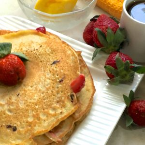 A stack of strawberry pancakes on a square white plate with plum strawberries scatter at one side and butter, milk and syrup in little glass or white bowls alongside
