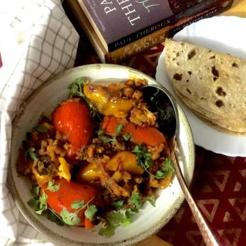 A round plate of stuffed Shimla mirch or coloured bell peppers stuffed with potato mash with a plate of chapatis, books and a checked napkin on the side