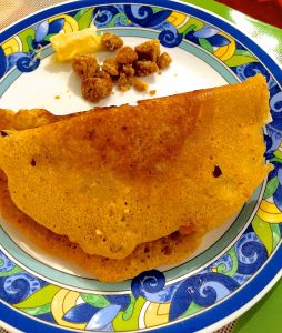 Multigrain adai thick crepes served on a  white plate edged in a blue and yellow pattern, with jaggery and butter