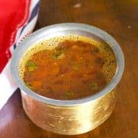 Brass vessel filled with reddish brown Tomato rasam. Pieces of tomato floating on top. A red and white napkin to the left, all of it on a brown wooden background