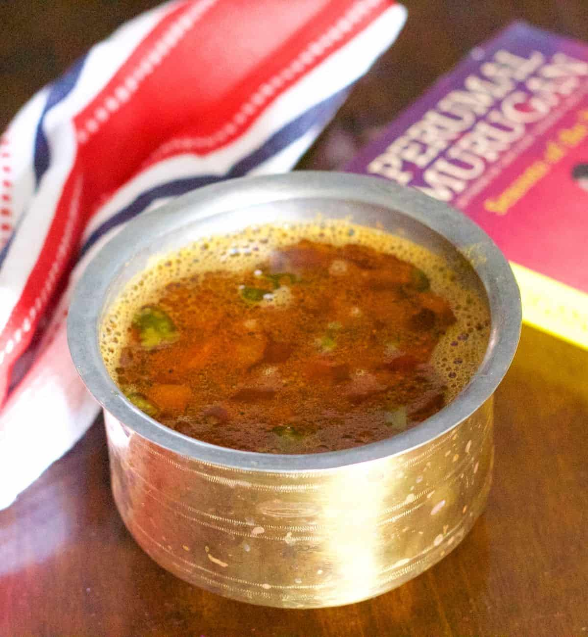 Reddish brown rasam in a brass vessel on a brown wooden background. Tomato slices seen floating on top. A red black and white napkin to the left and a book by Tamil author Perumal Murugan to the right, with a pink red cover
