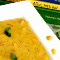 A broad white edged plate iwth yellow orangey vegetable corn chowder, garnished with mint leaves and flecked with black pepper. Green and yellow food books seen in the background