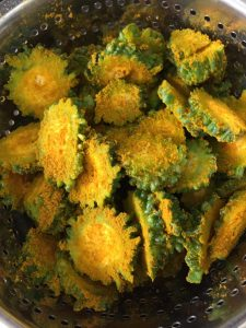 Round slices of bitter gourd or karela, marinated with turmeric and salt