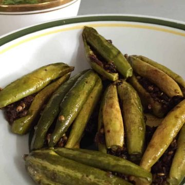 Pointed gourd stuffed with spices and sauteed. On a white plate with a green and yellow rim. Bharwan Parwal