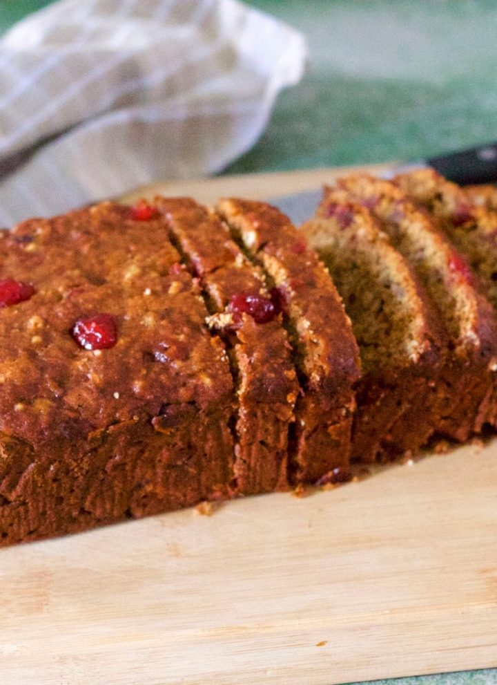 Red brown Banana Bread studded with bright red cranberries. sliced and placed on a light wooden cutting board. A pale grey cheked napkin behind, and a black knife handle seen to the right. All on a green background