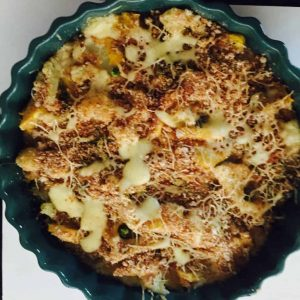 Baked vegetable au gratin in a green dish with scalloped edges. The top of the au gratin is brown and crusty