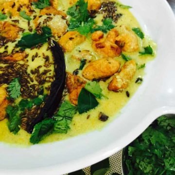 White rimmed bowl with yellow yogurt based kadhi with chickpea fritters and tempering of cilantro, cumin and red chilies