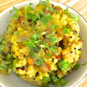 A bowl of bright yellow poha with peas and peanuts garnished with cilantro  and tempered with mustard