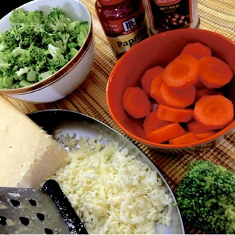 Ingredients for broccoli cheddar soup. Sliced carrots in an orange bowl, broccoli florets in a white bowl edged with gold, a plate with a grater and grated cheese