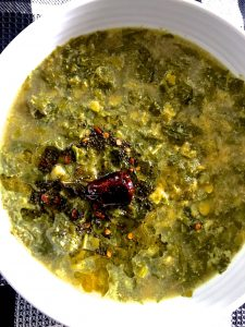Keerai kootu- South Indian Greens stew with lentils and cumin coconut paste in a white bowl