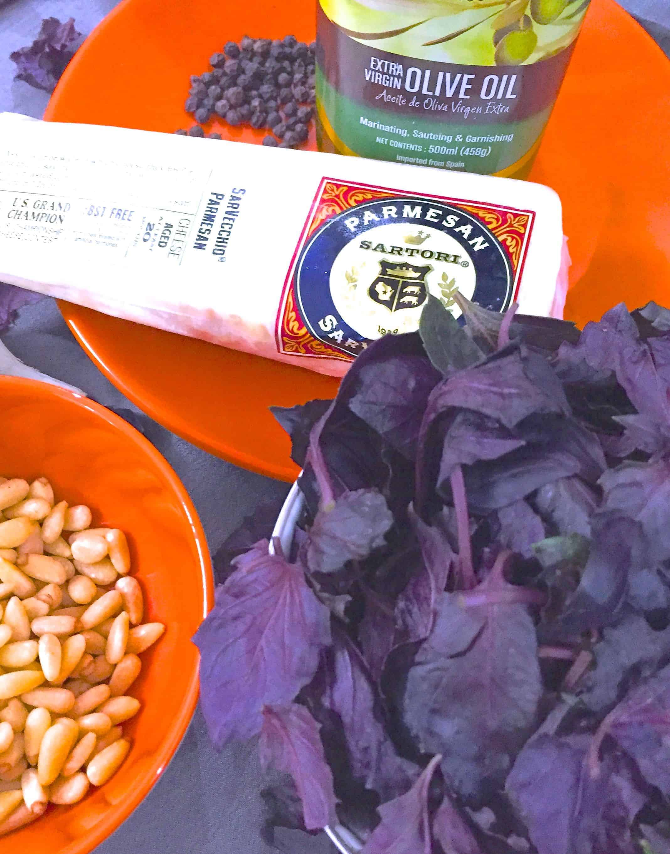Ingredients for making purple basil pesto. Dark purple basil leaves with a slab of parmesan, black peppercorns and virgin olive oil on an orange plate and pine nuts on an orange bowl