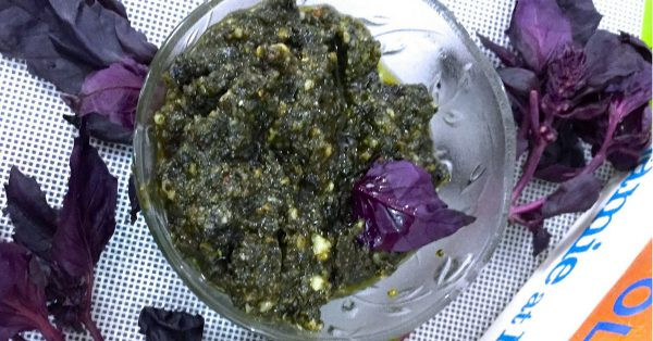 A glass bowl with a greenish Purple Basil Pesto with some Purple basil leaves alongside