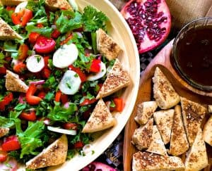 A plate of Fattoush Lebanese bread salad with traditional ingredients sumac, za'atar with pita bread, radish, tomato, greens and pomegranate molasses