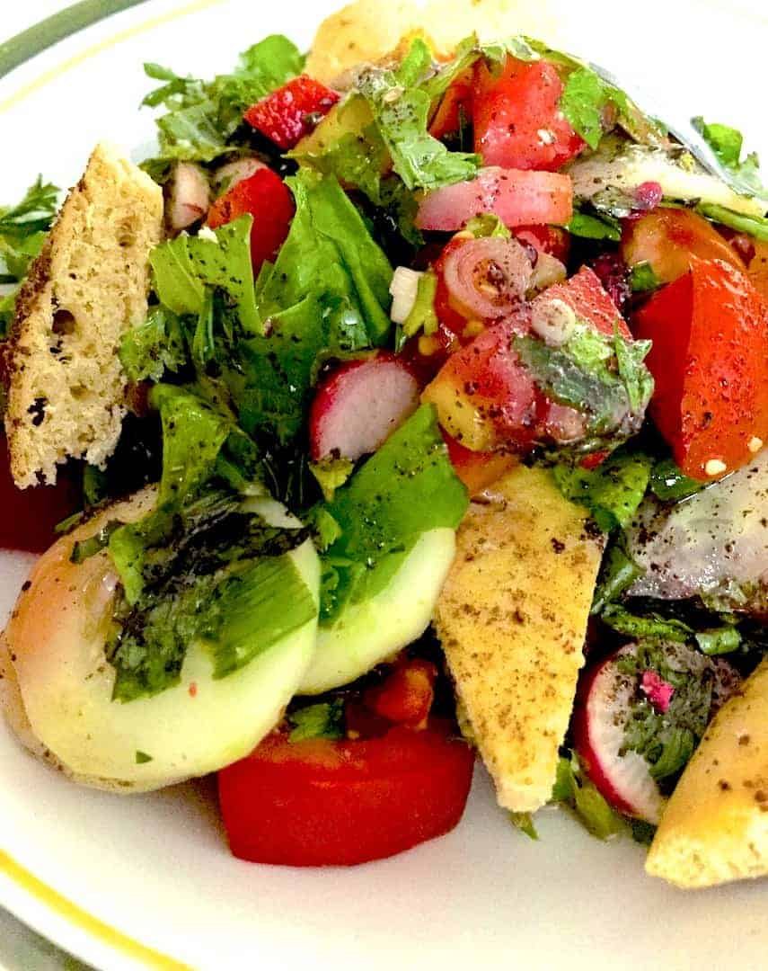 A plate of Fattoush the colourful Lebanese bread salad with Pita bread, tomatoes, red and white radish all sliced and dressed with pomegranate molasses and a lemon olive oil dressing