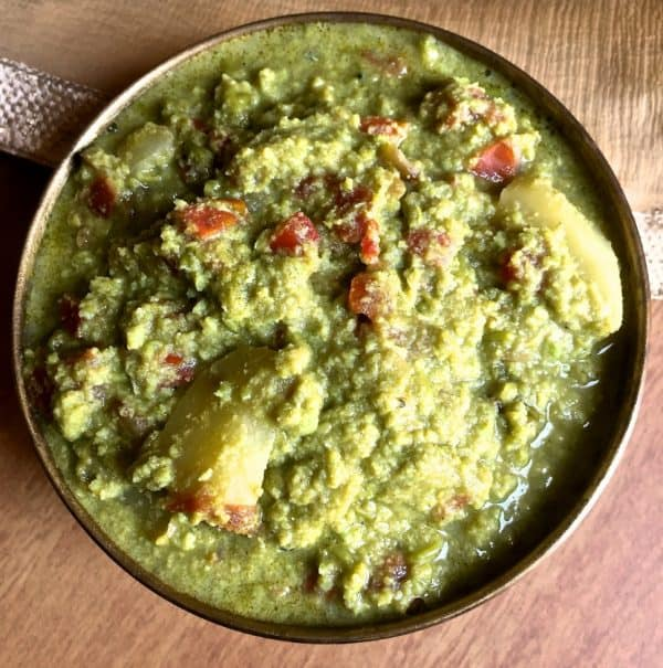 Matar ka Nimona, a fresh green pea and potato curry in a tomato onion spices gravy, in a round brass bowl on a light brown background.