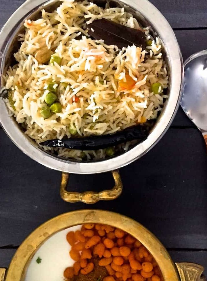 Matar ki Tehri - view from the top of a bowl of Green peas cooked with fragrant Basmati rice and spices, with another bowl with boondi raita and a long bass spoon alongside