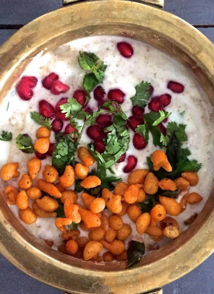 White Boondi Raita in a brass bowl, garnished with chickpea droplets, pomegranate arils and mint leaves