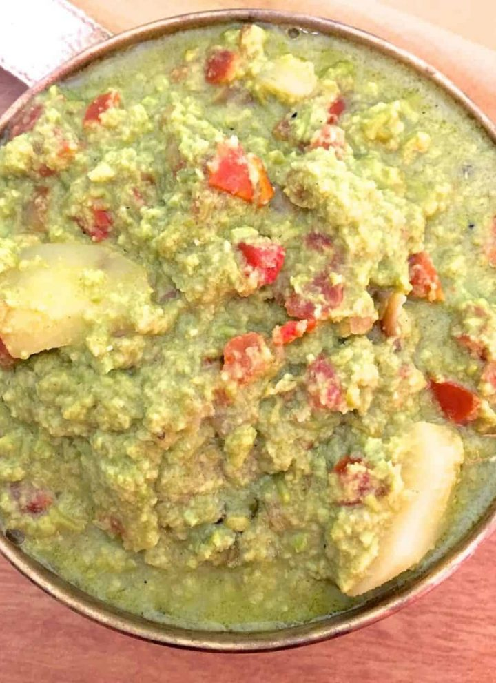 Green hued Green Pea curry with red tomato and chunks of potato showing through, in a round brass bowl. On a brick coloured background with a beige fabric in the background