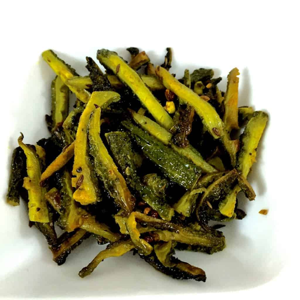 Overhead view of strips of green bitter gourd or karela, after frying with turmeric and salt