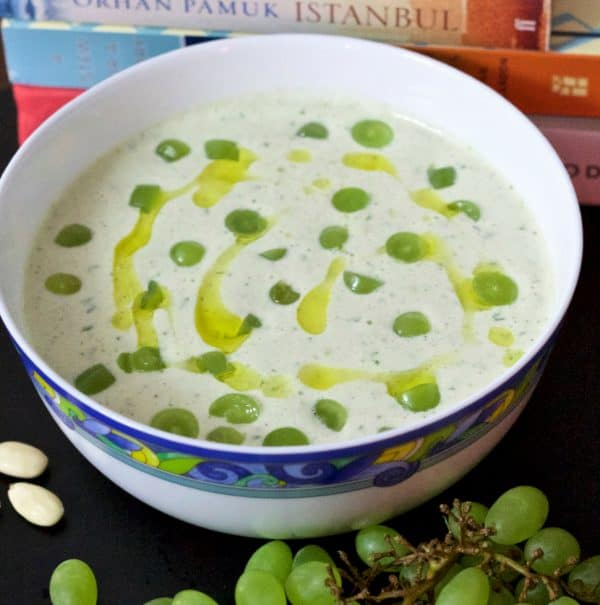 Chilled White Grape and Almond Gazpacho in white bowl edged with blue and yellow pattern, with green grapes and olive oil garnish. Green grapes and almonds on the foreground and books at the back including Istanbul by Orhan Pamuk
