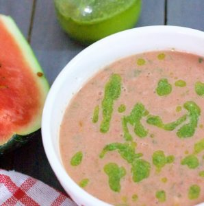 Pink Watermelon Gazpacho garnished with homemade Basil Oil, in a white bowl with a slice of watermelon on the left, a red checked napkin below and bottle of green basil oil in the background
