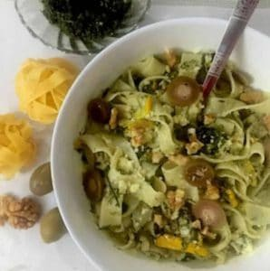 Fettucine fennel frond pesto in a white bowl, garnished with watlnuts and olives. Some fettucine pasta balls, walnuts and olives on the left side of the bowl and a glass bowl with pesto in the background