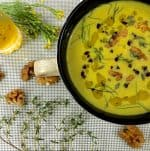 Yellow turmeric walnut fennel soup in a large cup with a handle on a white mat with yellow flowers and walnuts strewed alongside