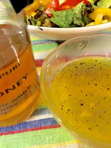 Bottle of honey next to a bowl of honey lemon garlickly salad dressing