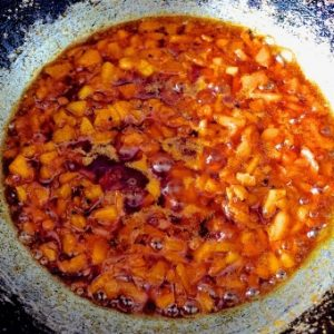 Making Raw Mango relish: a pan with mango slices coloured by the red chili powder, being cooked in oil, turmeric, mustard seeds
