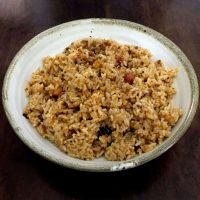 Brown hued Puliyodharai Tamarind Rice with peanuts on a white bowl with a thin beige edge, on a dark wooden background
