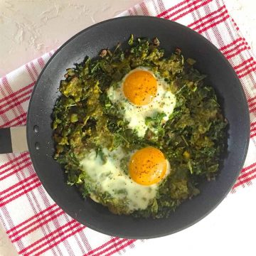 A pan of Green Shakshuka with Kale and Pesto with two open faced eggs, all on a red striped napkin on a white background
