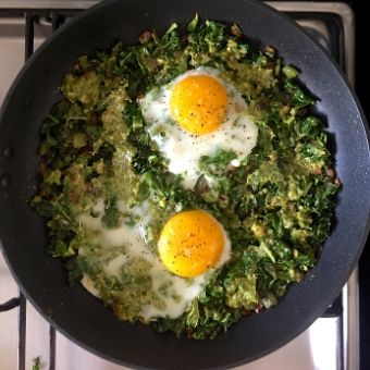 Green Shakshuka Process Shot 4: Add a layer of pesto and break two eggs on top