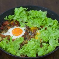 Shakshuka with sauteed red peppers and tomato and egg, surrounded by a bed of green lettuce