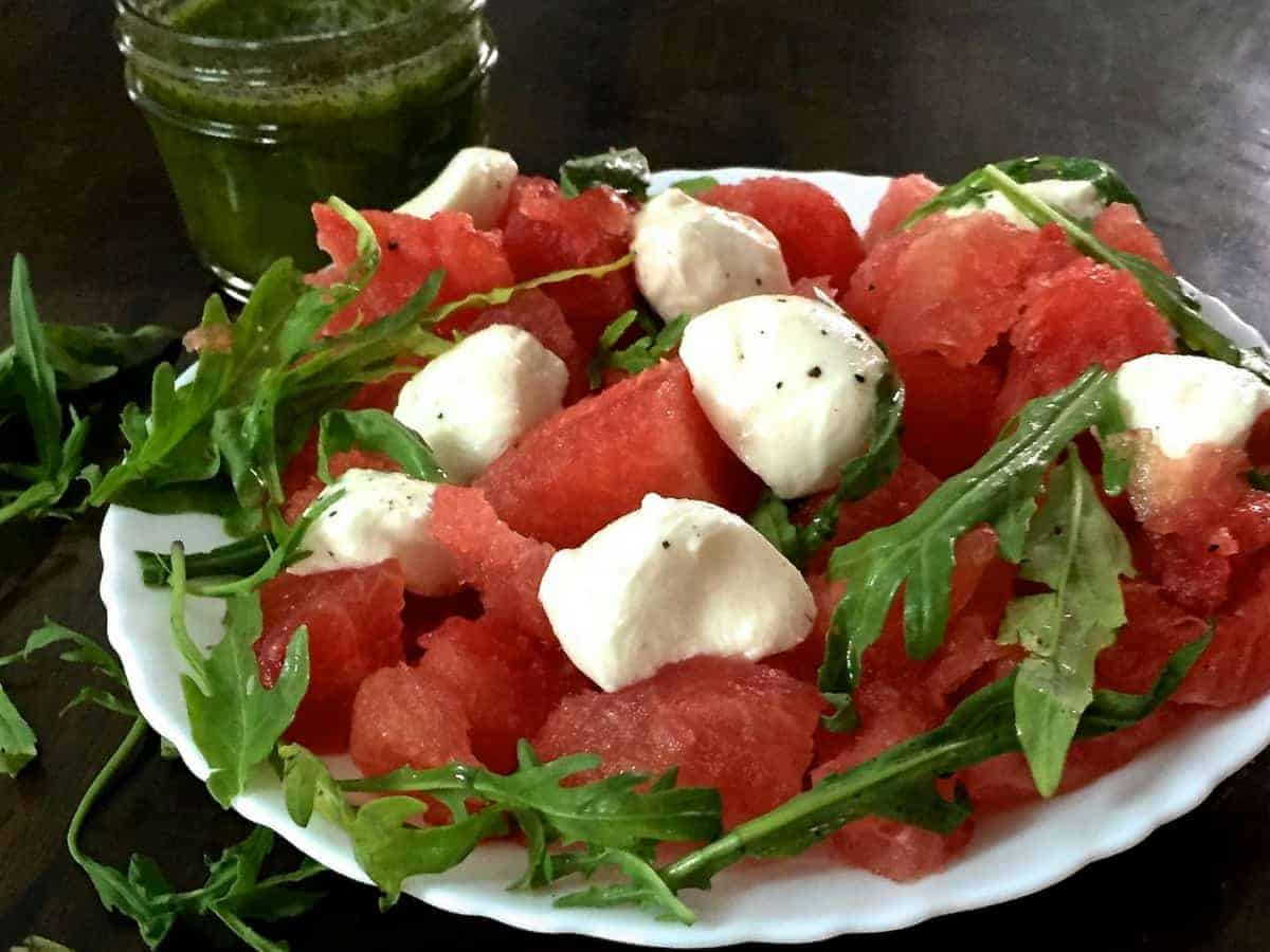 A white plate with a scalloped edge, filled with cubes of Watermelon and Halved Bocconcini cheese, with fresh arugual and pepper flakes for an easy cooling Watermelon Bocconcini Arugula Salad with Homemade Basil Oil