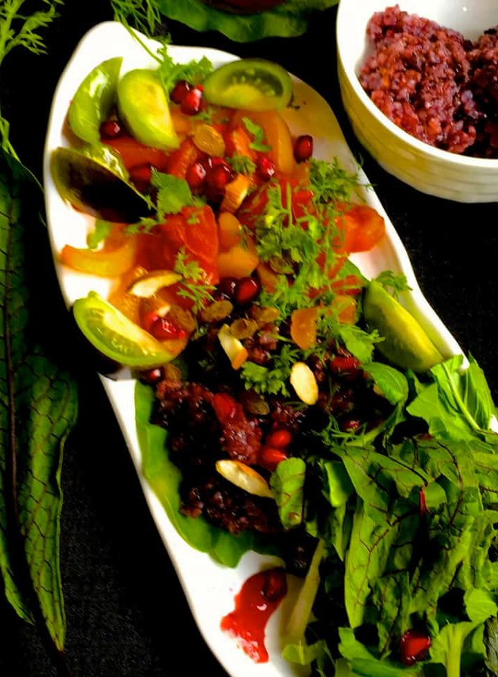 Black Rice Salad with fresh greens and herbs and a cranberry orange dressing on a boat shaped white plate with a white bowl for the dressing