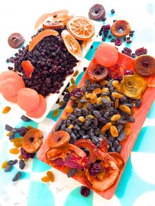 A variety of dry fruits for soaking for a Christmas cake, on an orange plate with a blue and white backgroun