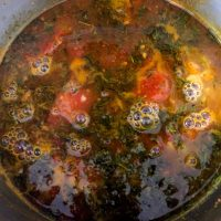Bringing the thyme rasam to a boil.