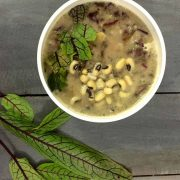 Thick french style 2 bean sorrel soup granished with red sorrel leaves and black eyed peas seen on the surface. Red sorrel leaves in the foreground, all on a wooden background