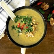 Overhead view of a cup of yellow curried chilli zucchini soup, garnished with slices of red chillies, coriander, parsley and mint leaves and walnuts. A white napkin striped with dark blue to the left, and walnuts and red chillies to the right