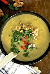 A cup of mustardy yellow Chilli Zucchini Soup with Walnuts and curried with chilli powder and Turmeric. Garnished with red chilli slices, walnuts and fresh herbs