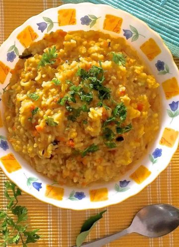 Bright yellow khicidi for the new mom, made from rice and lentils cooked together with vegetables, garnished with coriander leaves, on a white plate with a yellow and blue design at the edge. Coriander leavs and a steel spoon in the foreground. A blue green napkin on the top left and all set on ayellow mat