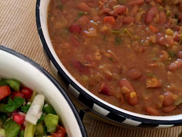 Flavourful Nutritious Rajma Masala Curry of red kidney beans in a thick tomato onion gravy in checkered black and white bowl with salad by the side