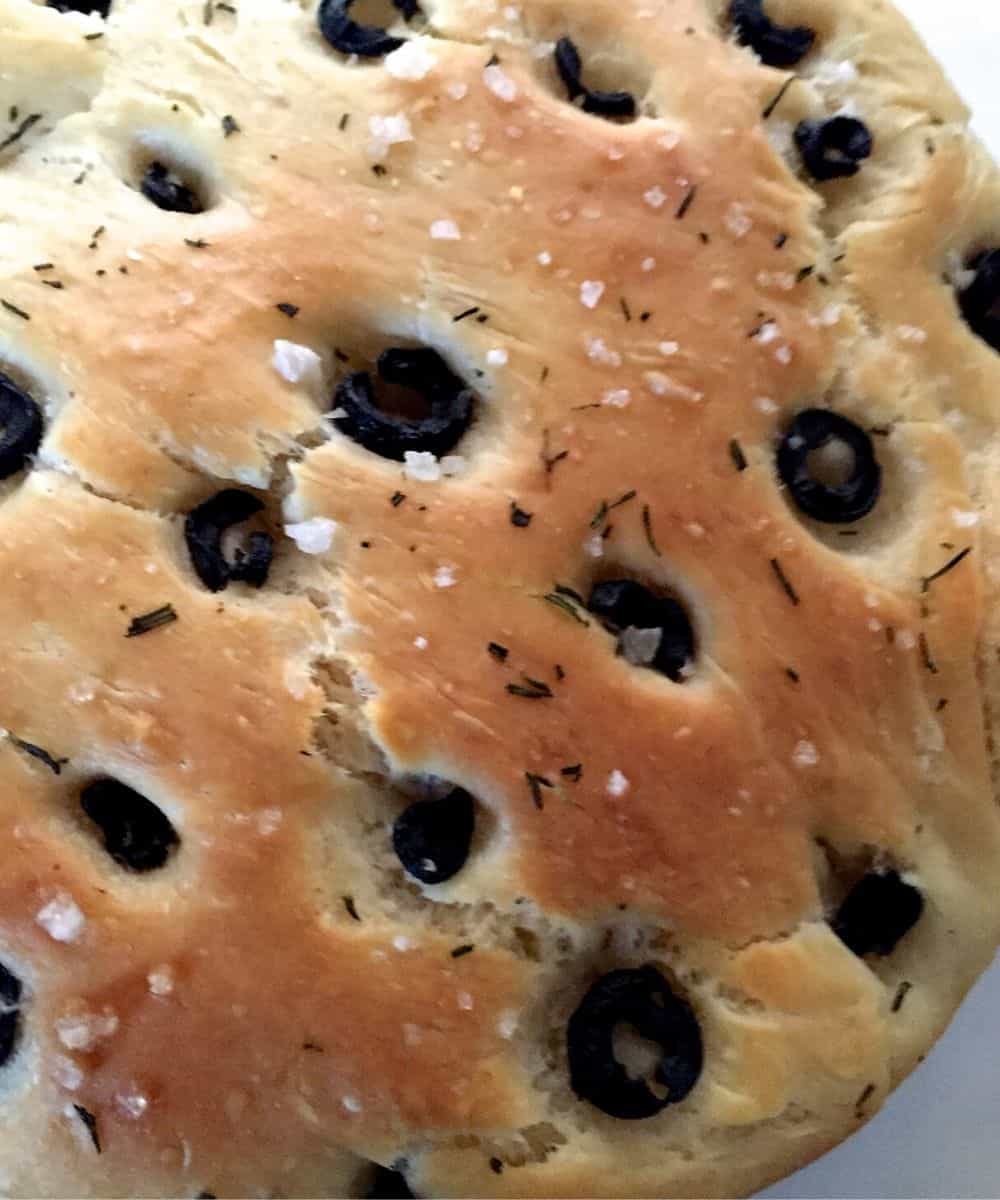 Well baked crusty olive rosemary focaccia with specks of salt seen among the olives and bits of rosemary