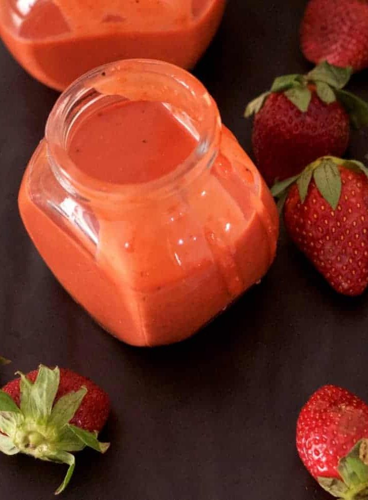 2 little glass jars of orangey pink strawberry poppyseed salad dressing, with strawberries strewn around on a black background