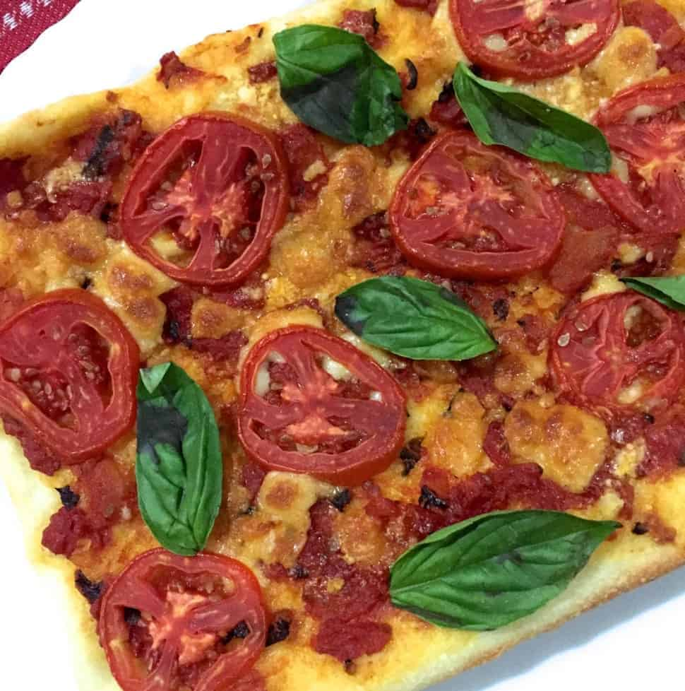 Thin crust tomato mozzarella pizza with slices of red tomato, mozzarella cheese and fresh basil leaves